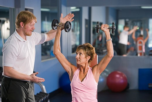 Middle-aged woman lifting weights at gym personal trainer : Stock Photo