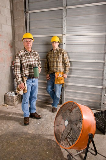 Men wearing hardhats holding thermos at construction site : Stock Photo