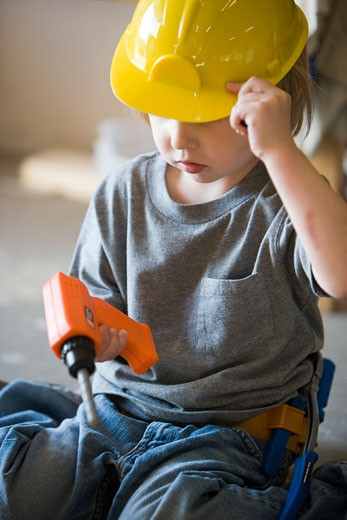 Little boy playing with hard hat and toy drill : Stock Photo