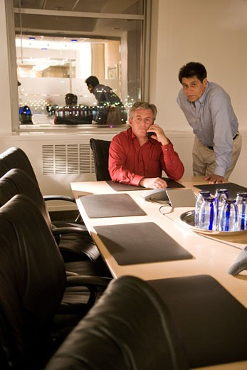 Two multi-racial businessmen in boardroom at night working late : Stock Photo