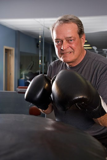 Stock Photo: 1785-10883 Portrait of senior man with boxing gloves at gym