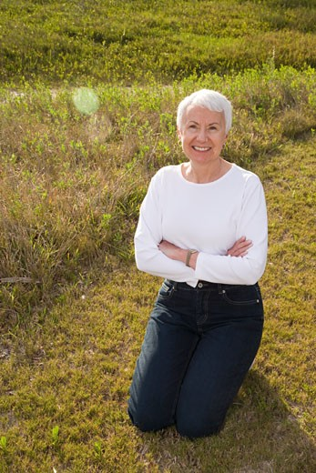 Senior woman smiling, kneeling on grass in park : Stock Photo