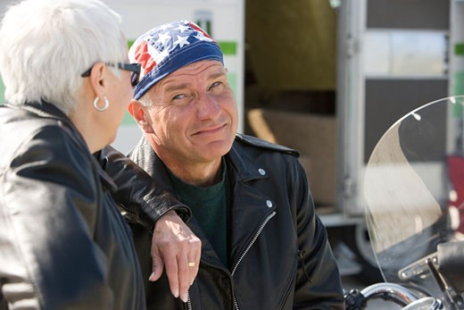 Stock Photo: 1785-11015 Close-up of senior couple sitting on motorcycle next to RV camper