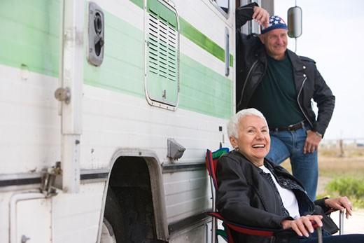 Happy senior couple outside RV camper : Stock Photo