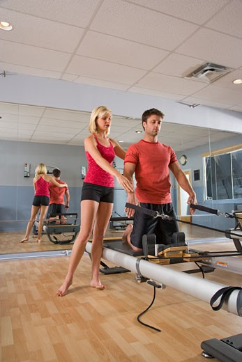 Stock Photo: 1785-11176 Young couple on Pilates exercise equipment in gym