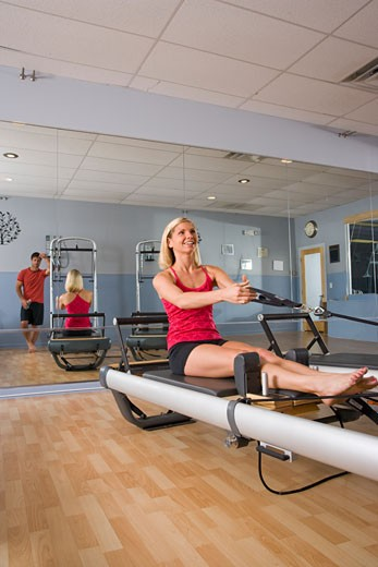 Young woman working out on Pilates exercise equipment in gym : Stock Photo