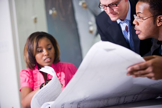 Three multi-racial colleagues reviewing floorplans : Stock Photo
