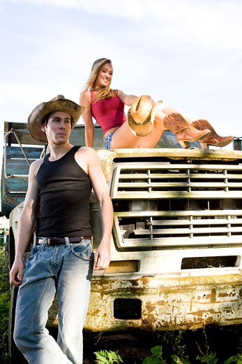Young couple with cowboy hat and boots on old truck : Stock Photo
