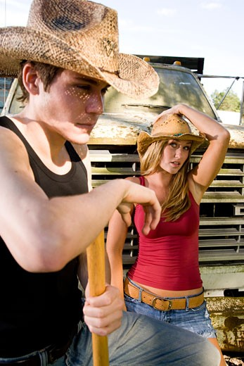Young woman sitting on truck and young man wearing cowboy hats : Stock Photo