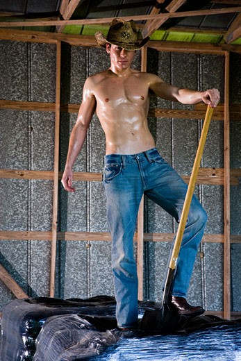 Stock Photo: 1785-11447 Young man in denim and cowboy hat, standing in barn