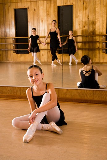 Portrait of a young ballerina sitting on floor in dance studio : Stock Photo