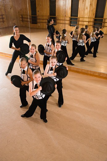 Group of girls in costume rehearsing in dance studio with teacher : Stock Photo