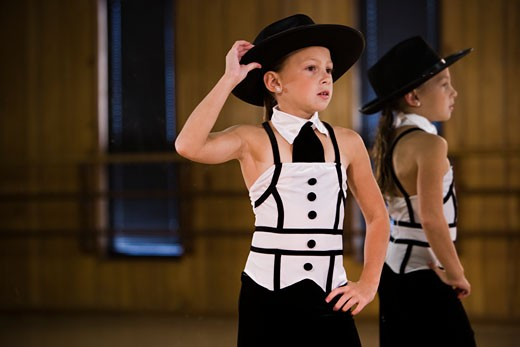 Stock Photo: 1785-11577 Girl in costume posing in dance studio with mirror in background