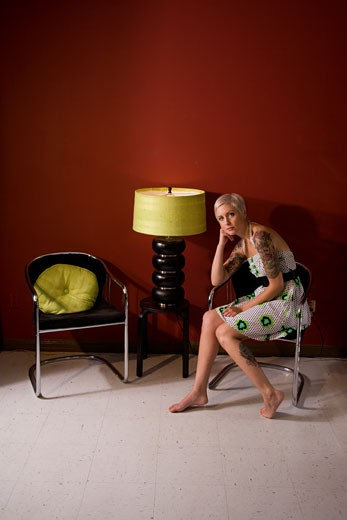 Stock Photo: 1785-11671 Young woman with tattooed arm sitting on chair