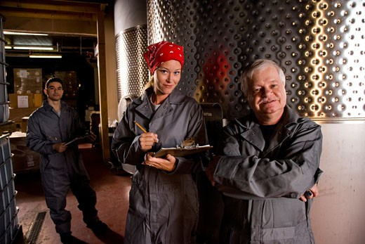 Winery workers standing next to wine vats : Stock Photo