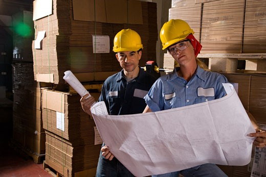 Two workers standing in storage warehouse looking at plans : Stock Photo