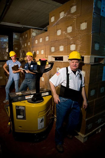 Three workers in hard hats in storage warehouse : Stock Photo
