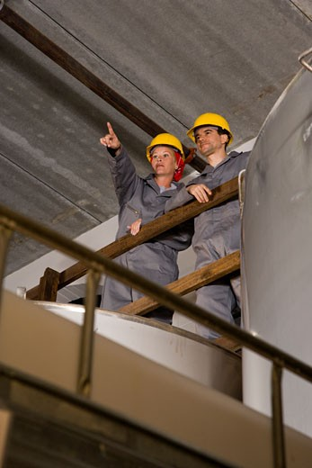 Blue-collar workers in factory overlooking storage tanks : Stock Photo
