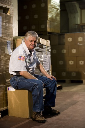 Male worker sitting on a box in a storage warehouse : Stock Photo