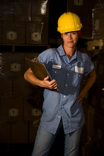 Femaie worker wearing hard hat standing in storage warehouse : Stock Photo