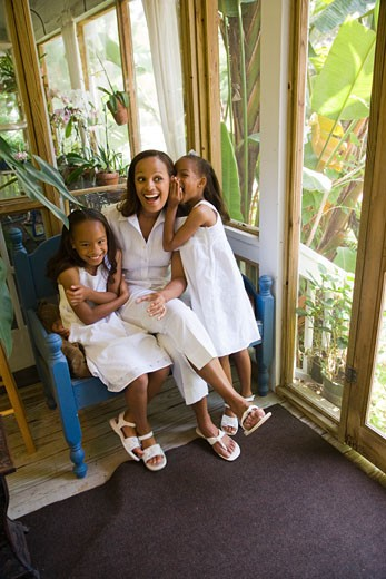 Happy African-American mother and daughters in sunroom whispering : Stock Photo