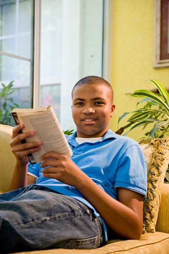 African American teenage boy reading book on couch : Stock Photo