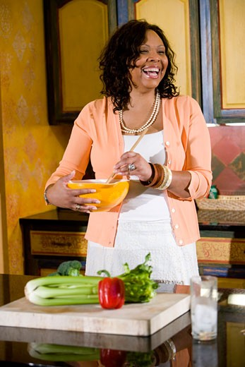 Middle-aged African-American woman stirring bowl in kitchen : Stock Photo