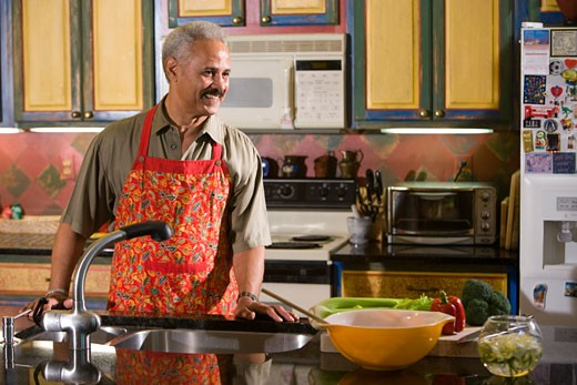 Middle-aged African-American man in kitchen preparing meal : Stock Photo