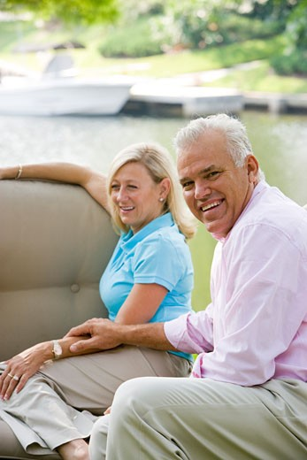 Portrait of middle-aged couple sitting on sofa outside, with boats in background : Stock Photo