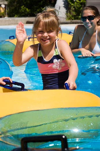 Girl sitting on innertube at waterpark waving, mother smiles in background : Stock Photo