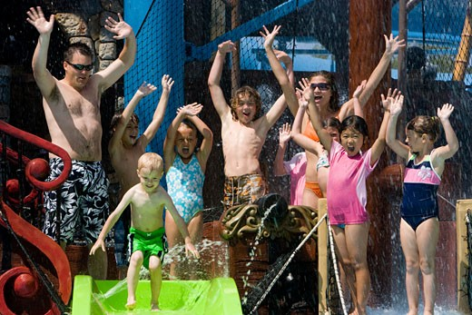 Stock Photo: 1785-12349 Family and friends waving at waterslide in water park