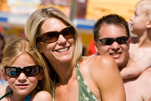 Headshot of family wearing swimsuits and sunglasses on sunny day : Stock Photo