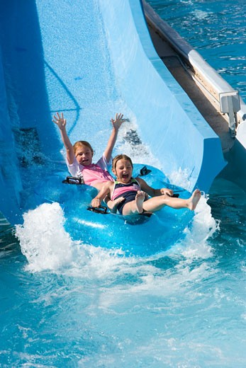 Stock Photo: 1785-12374 Girls sliding down waterslide on innertube in water park