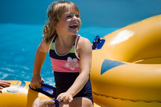 Stock Photo: 1785-12382 Young girl sitting on an innertube at a water park laughing