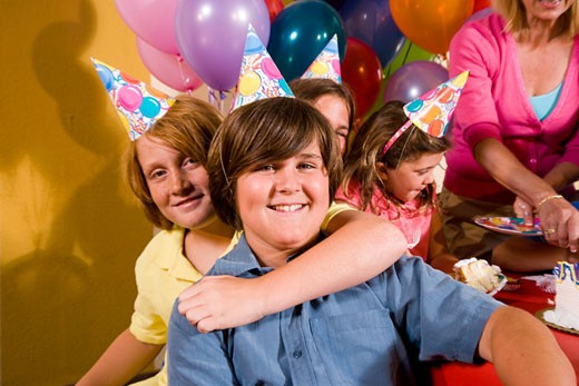 Boys playing at birthday party wearing party hats : Stock Photo