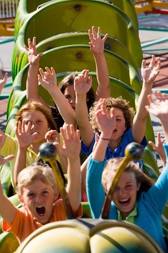 Children riding a roller coaster in an amusement park : Stock Photo
