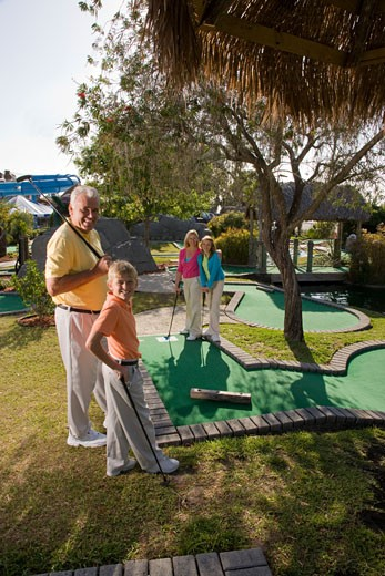 Stock Photo: 1785-12514 Family playing miniature golf