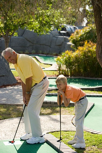 Father and son playing miniature golf : Stock Photo