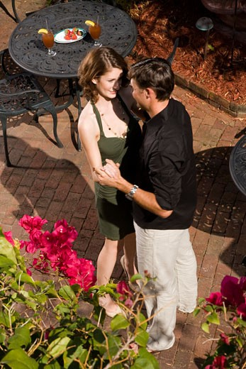 Romantic couple dancing in garden patio : Stock Photo
