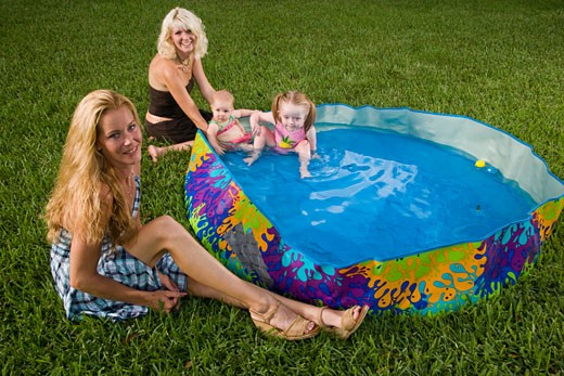 Young women with baby and girl in kiddie pool sitting in backyard : Stock Photo