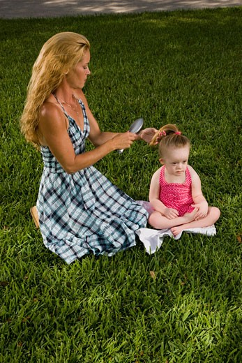 Stock Photo: 1785-12789 Mother combing hair of daughter with downs syndrome