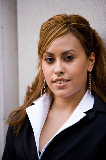 Heashot of Hispanic businesswoman smiling outside office building : Stock Photo