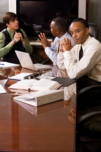 Stock Photo: 1785-13276 Multi-racial businessmen working in office conference room on paperwork