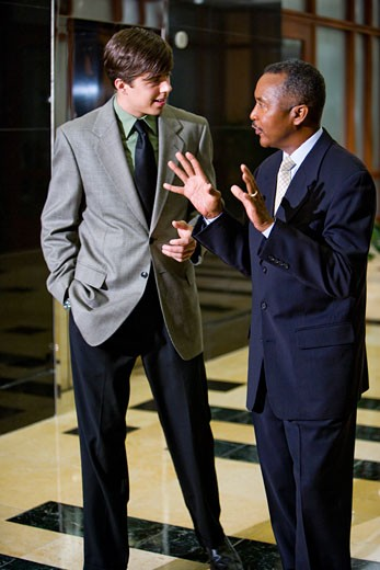 African-American businessman with talking young colleague in office lobby : Stock Photo