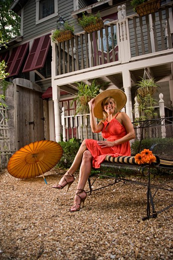 Woman wearing wide-brimmed hat sitting in a garden patio : Stock Photo