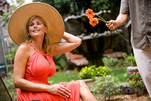 Stock Photo: 1785-13512 Woman wearing wide-brimmed hat sitting in a garden patio