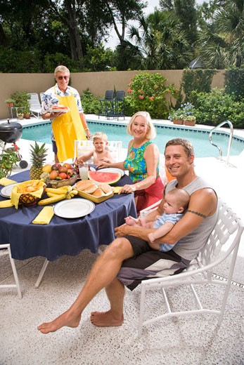 Stock Photo: 1785-13542 Portrait of three-generation family sitting by swimming pool