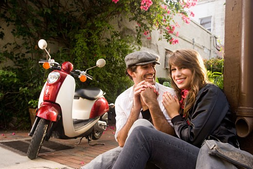 Young couple sitting on street holding hands next to motor scooter : Stock Photo