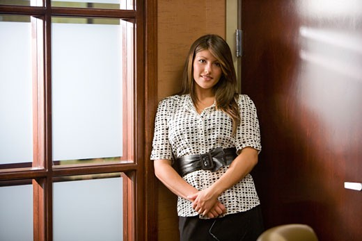 Hispanic businesswoman standing in office : Stock Photo