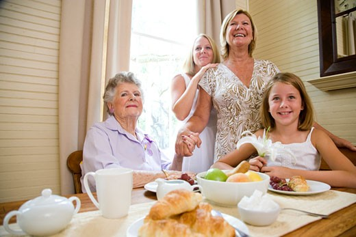 Four generations of women at breakfast table : Stock Photo